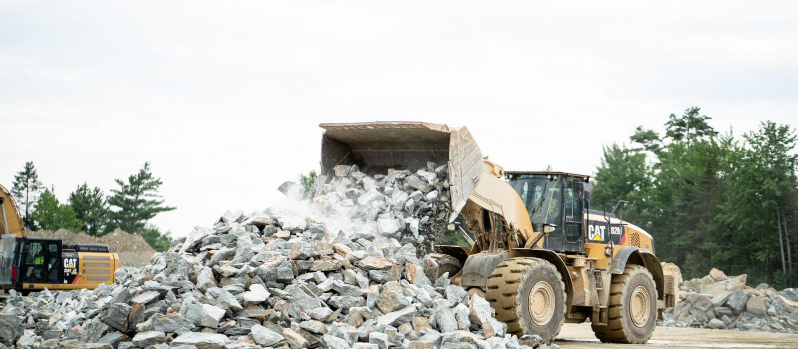 Large Excavators Dumping Pile Of Large Rocks